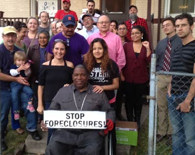 Jerome Jackson in wheelchair in front of group in front of house with sign - stop foreclosures