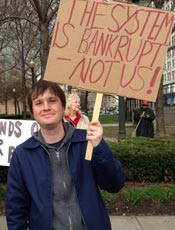 Protester with sign - the system is bankrupt - not us!